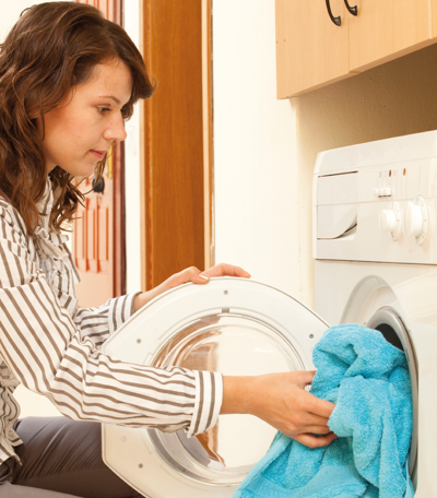 A woman filling a washing machine