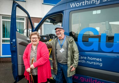 A day centre user and a transport volunteer in front of one of Guild Cares buses
