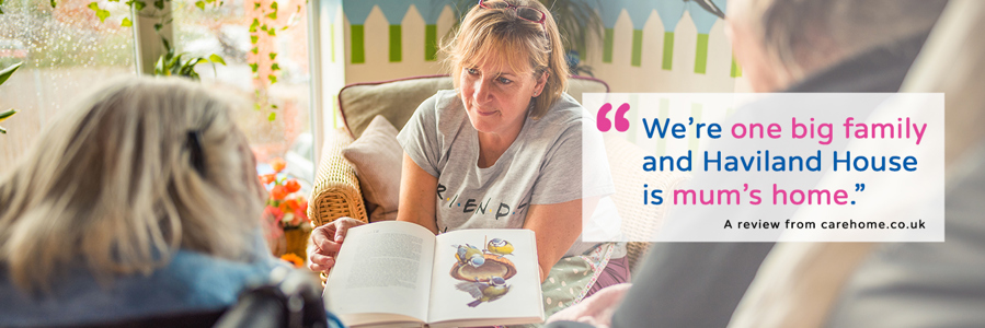 A Haviland House staff member reading to two family members in the homes Ashmount Garden Room. On top of the image is the text: Were one big family and Haviland House is mums home. - A review from carehome.co.uk
