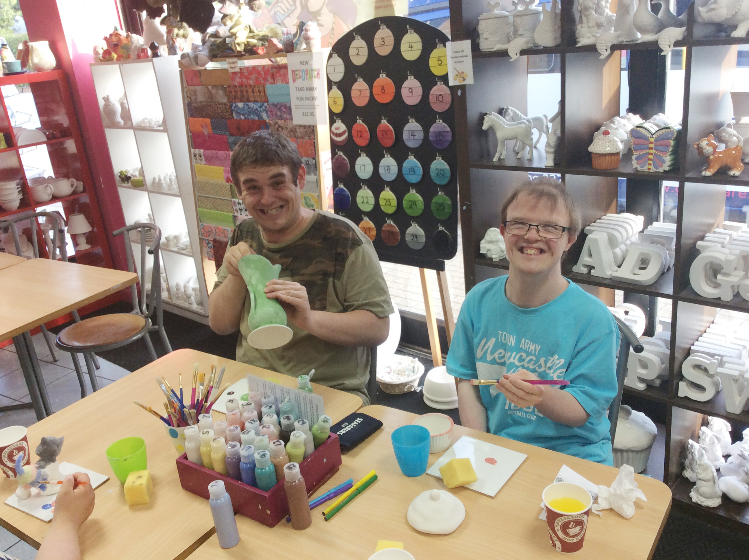 Ashdown Extra club for 18 to 30 with a disability or additional needs. Two young men painting pottery.