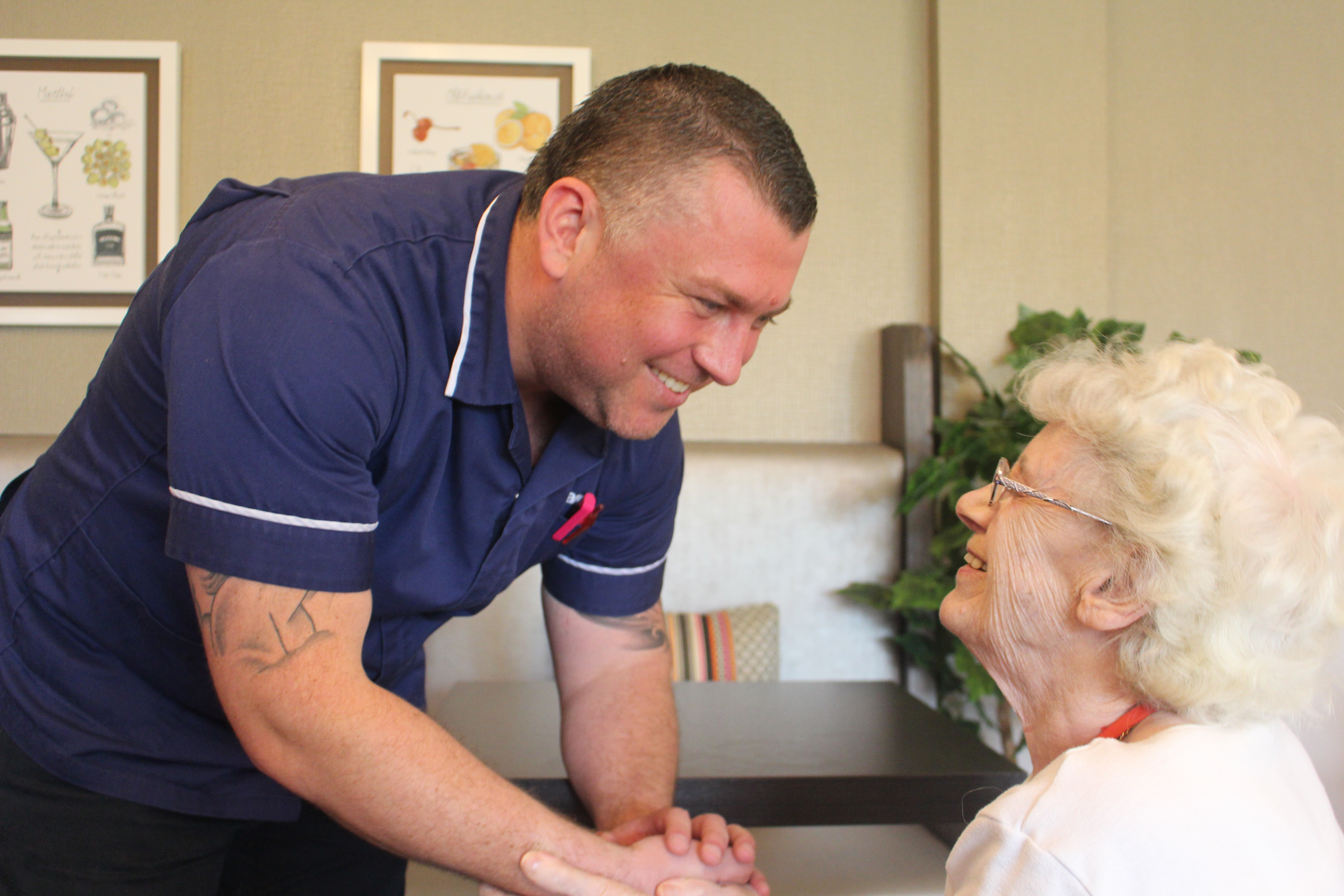 A nurse bending over and holding the hands of a care home resident.