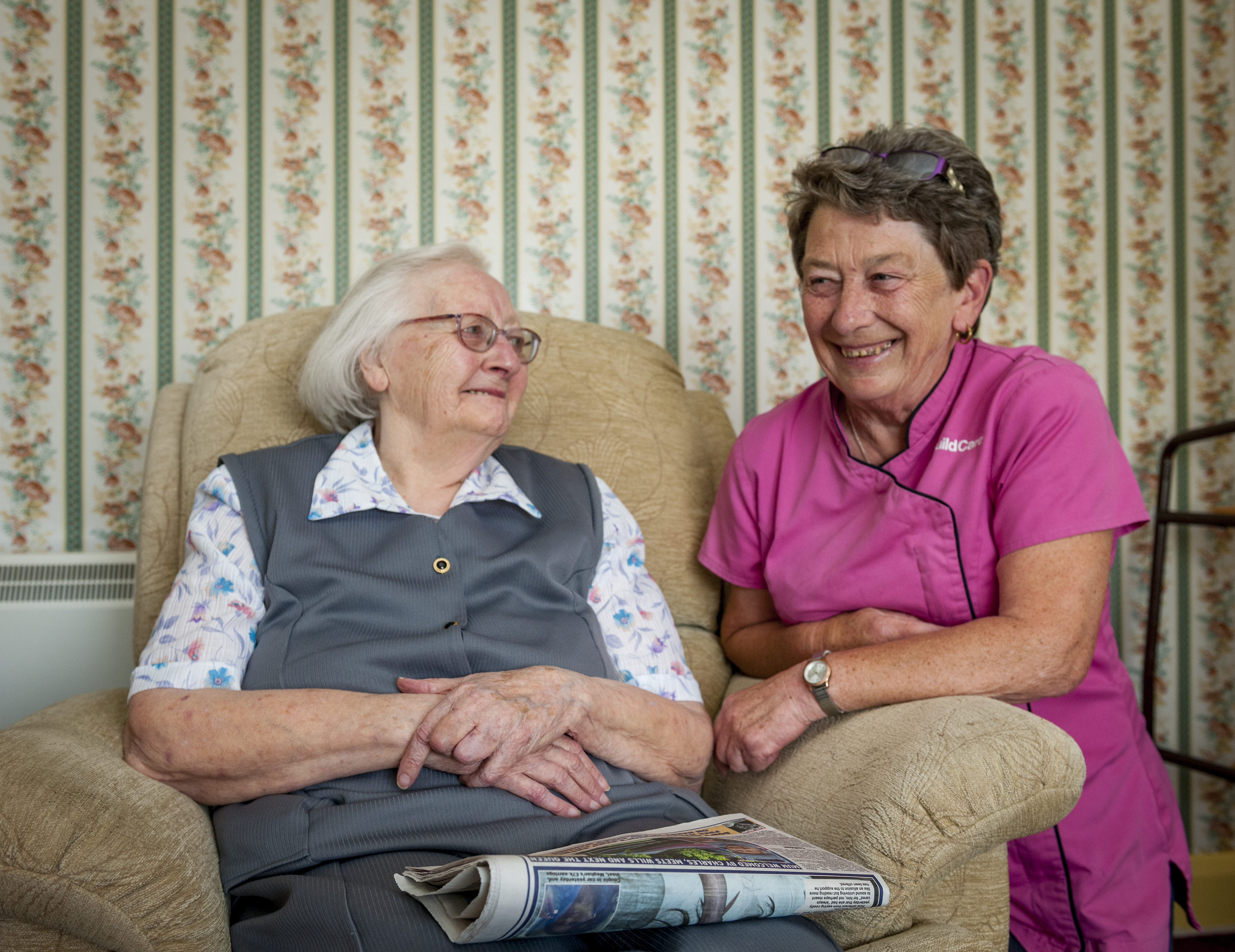 Guild Care home care assistant with one of her clients smiling and reading the newspaper