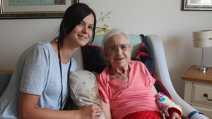 Haviland House. A care home resident sat in an armchair. Beside her is a care assistant.