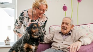 A Haviland House family member sat in a chair with a dog. Stood beside him is a staff member.