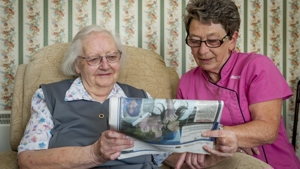 A Community Care Assistant sat with a client. They are reading a newspaper together.