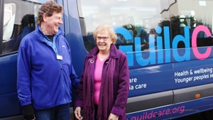 A female day centre user with a male Guild Care transport volunteer standing in front of a minibus
