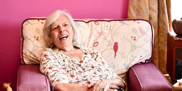 An elderly lady sat in an armchair, smiling