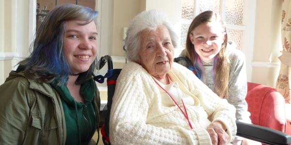 A care home user sat in a wheelchair surrounded by two female teenagers