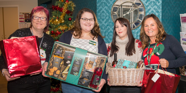Jodie Hoskins and her Helena Sherriff present Christmas boxes to Guild Cares Customer Service Team
