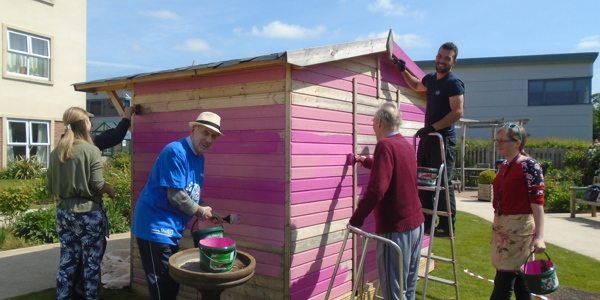 Five people painting a shed