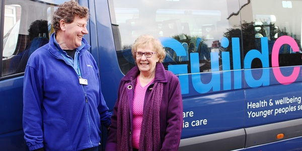 A day centre user standing in front of a Guild Care mini bus with a transport volunteer