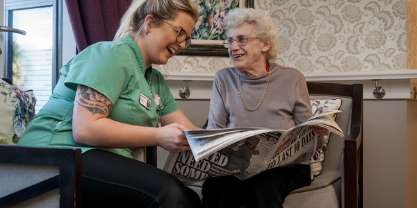 A Care Assistant and a female Caer Gwent resident sat in armchairs reading a newspaper together.