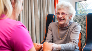 A Caer Gwent Care Assistant holding hands with a resident
