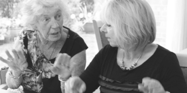 An older woman and a younger woman talking in black and white