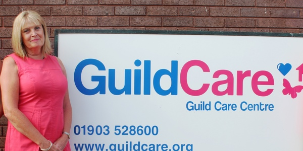 Antonia Hopkins, Guild Cares Interim Chair, in front of a Guild Care sign