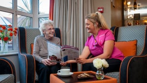 A care worker talks to a Caer Gwent resident in the homes lounge