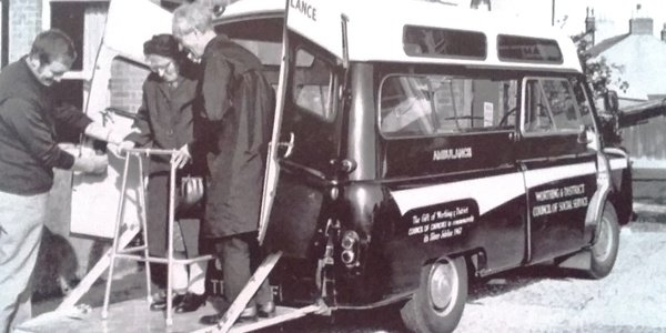Black and white photo of a woman with a zimmer frame exiting the back of an ambulance